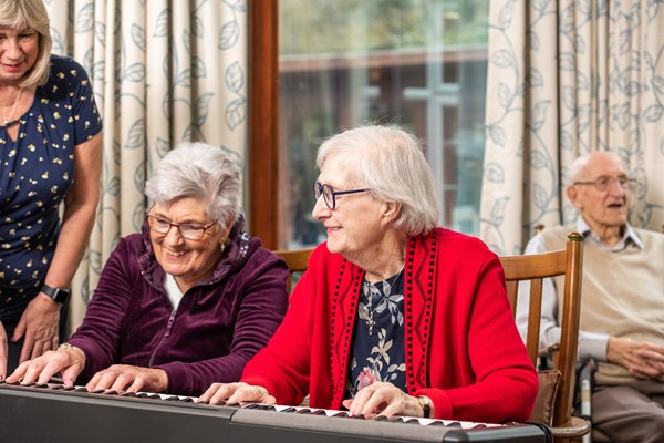 Residents smiling and happy playing the keyboard at Culver House