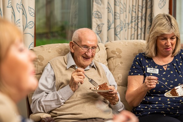 Culver House resident and staff enjoy eating slices of cake together