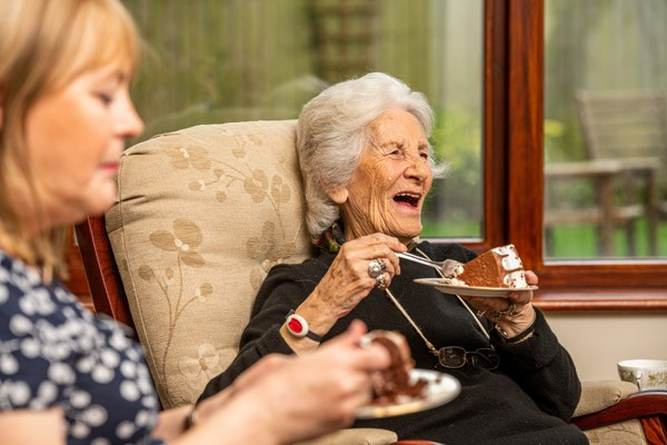 Resident at Culver House smiling whilst enjoying her chocolate cake