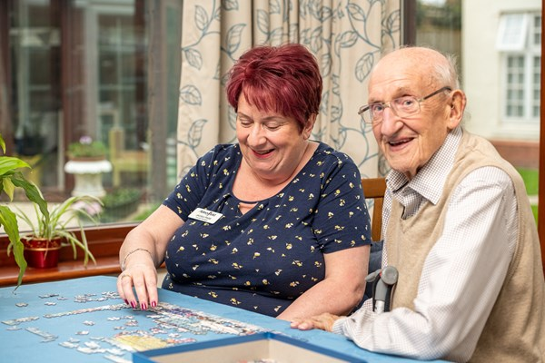 Smiling resident and member of staff do a puzzle together